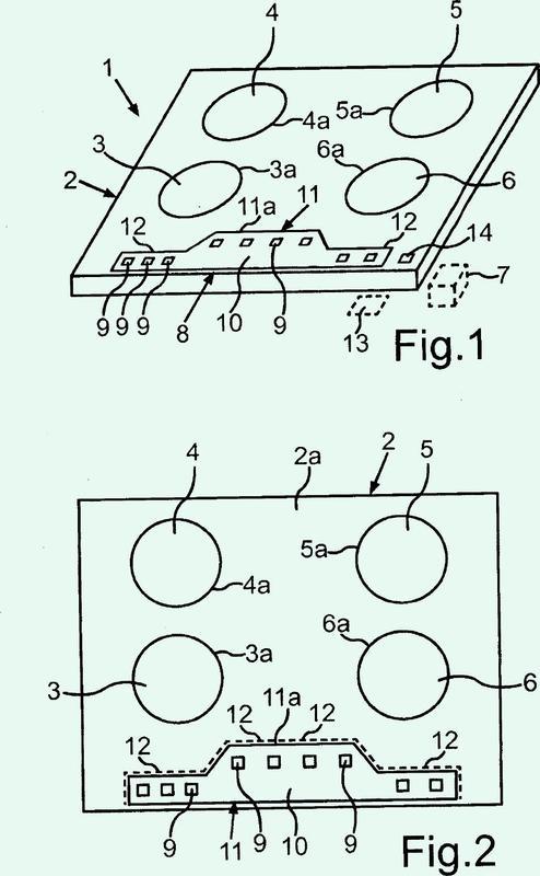 Campo de cocción con una placa de campos de cocción y con una banda de conductores como limitación de la superficie para componentes electrónicos.